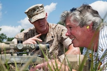 Christopher Hayes, chairman of the board and Revere Bank chair for Vistage International, Inc. in Laurel, Md., receives instruction from Sgt. Jason Wattle,a  rifleman, about firing an M-40 sniper rifle aboard Marine Corps Base Quantico on July 18, 2014. Hayes fired the weapon during a portion of the Marine Corps Executive Forum, an event held several times a year to introduce the Marine Corps to civilians in leadership roles.