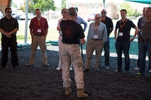 Retired Lt. Col. Joseph Shusko, director of the Marine Corps Martial Arts Center of Excellence, explains MCMAP techniques and philosophy to the participants of the Marine Corps Executive Forum on July 18, 2014. Seventeen civilian leaders attended the forum, learning about various aspects of the Marine Corps.
