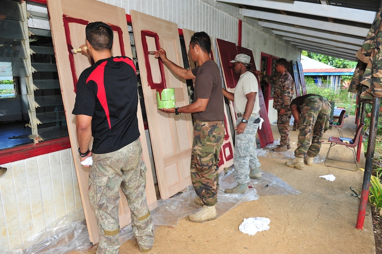 New Zealand, Tongan and American military members paint doors July 17, 2014, at the Toula Government Primary School, Toula, Tonga. Military members made several repairs at five schools including the replacement of doors, locks, windows, wiring, partitions, sinks, faucets and toilets during Operation Pacific Angel-Tonga. (U.S. Air Force photo/Staff Sgt. Rachelle Coleman)