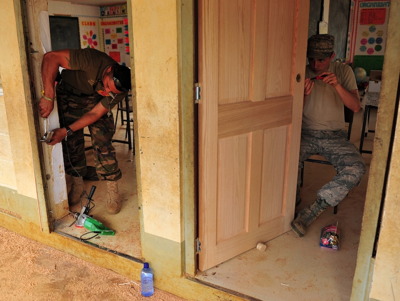 Tongan armed forces Pvt. Benny Kalonihea, left, and Airman 1st Class Devin Laird replace doors July 17, 2014, at the Neiafu Government Primary School, Neiafu, Tonga. Military electricians, structural craftsmen, carpenters and plumbers worked together to repair and replace doors, locks, windows, wiring, partitions, sinks, faucets, toilets and various additional requirements during Operation Pacific Angel-Tonga. Pacific Angel is a total force, joint and combined humanitarian assistance operation, led by Pacific Air Forces. Kalonihea is a carpenter and Laird is an electrician. (U.S. Air Force photo/Staff Sgt. Rachelle Coleman)
