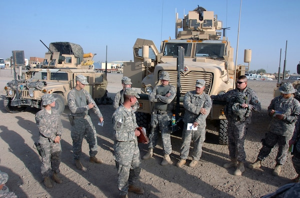 Citizen-Soldiers with the Kentucky National Guard's 223rd Military Police Company conduct a briefing at Camp Liberty, Iraq, before an escort mission in 2008 in front of their vehicles. (Army National Guard photo by Staff Sgt. Jim Greenhill)