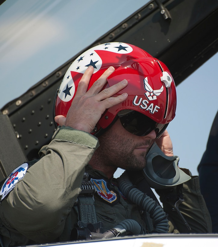 Wes Welker, Denver Broncos wide receiver, puts on a flight helm and mask July 20, 2014, before his flight with the U.S. Air Force Thunderbirds. Welker was one of two participants given the opportunity to ride in the passenger seat as a Thunderbirds pilot performed aerial maneuvers. (U.S. Air Force photo by Airman 1st Class Brandon Valle)