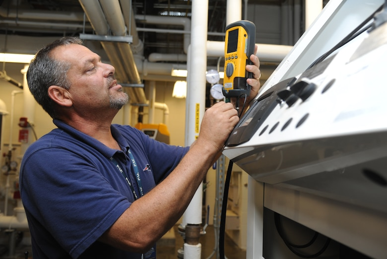 John Grant, Base Operations Support contractor, uses an Ultrasonic Inspection System and Flow Meter that improve system monitoring and calibration inside the 41st Aerial Port building mechanical room July 18, 2014, at Keesler Air Force Base, Miss. This system is utilized as part of the Reliability Centered Maintenance program which evaluates equipment performance piece by piece to determine wear and lifecycle of each item.  The goal of the program is to institute the most cost effective plan for maintaining complex systems and minimize equipment failure or downtime. (U.S. Air Force photo by Kemberly Groue)