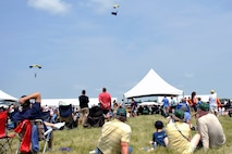 Air show patrons sit in the grass and watch as the U.S. Navy Leap Frogs parachute demonstration team comes in for a landing at the 2014 Defenders of Freedom Open House and Air Show July 19 at Offutt Air Force Base, Nebraska.  The Leap Frogs represent Naval Special Warfare and the U.S. Navy.  The members of this team must be military freefall qualified, be serving on at least their second enlistment, have completed at least two operational deployments and be recommended by their chain of command.  (U.S. Air Force photo by Jeff W. Gates/Released)