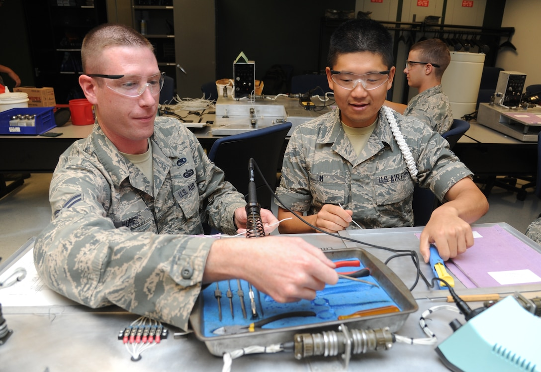 Staff Sgt. Benjamin Huff and Airman 1st Class Brian Um, 335th Training Squadron, use trainers for review during the avionics fundamentals course July 21, 2014, at Dolan Hall, Keesler Air Force Base, Miss. Huff and Um graduated with perfect scores.  Huff, from Kuna, Idaho, will return to the 124th Maintenance Squadron, Gowen Field Air National Guard, Idaho.  Um, from Whittier, Calif., will receive follow-on training in the 365th Training Squadron at Sheppard Air Force Base, Texas. (U.S. Air Force photo by Kemberly Groue)