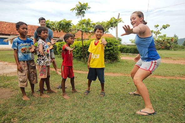 """Cadet 2nd Class Hansena Vangen teaches Cambodia children the """"Hokey Pokey"""" during a recent Academy Cultural Immersion Program trip to Cambodia. While there, the cadets built latrines in Cambodian villages, took in historical sites and spent time with Cambodian citizens. (U.S. Air Force photo)"""