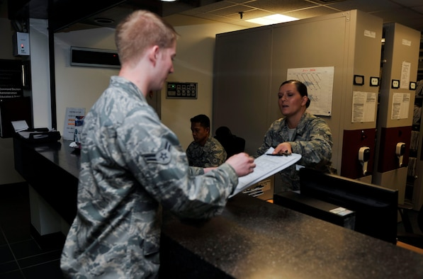 Staff Sgt. Jennifer Romine, 51st Dental Squadron readiness NCO in charge, hands examination paperwork to Airman 1st Class Tanner Peterson, 51st Logistics Readiness Squadron refueling mechanic, prior to his annual exam on Osan Air Base, Republic of Korea, July 16, 2014. The 51st DS sees approximately 100 to 130 patients daily. (U.S. Air Force photo by Senior Airman David Owsianka)