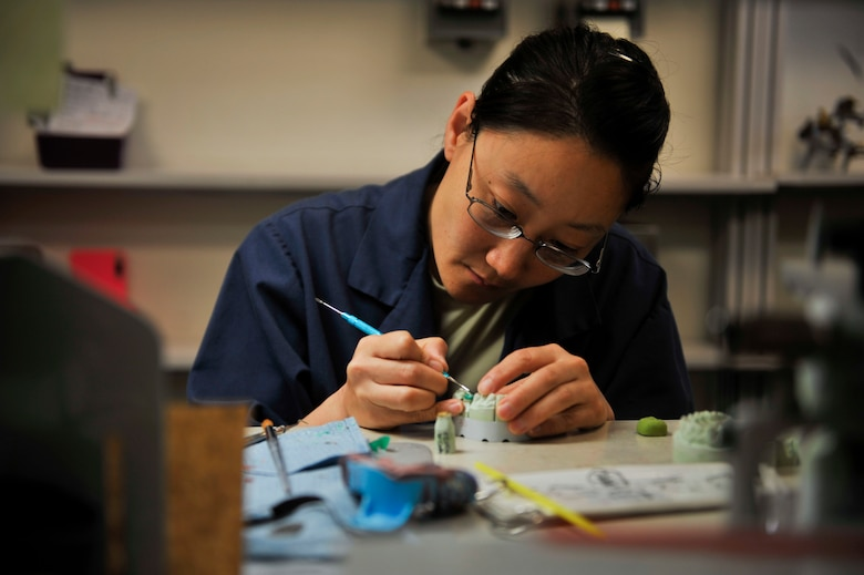 Staff Sgt. Janine Sung, 51st Dental Squadron laboratory technician, uses an instrument to evenly place wax around a stone mold tooth to provide a crown for a patient's tooth on Osan Air Base, Republic of Korea, July 16, 2014. Once completed, a dentist will trim away the unfavorable area on the tooth of a patient to place the new crown on top of it. (U.S. Air Force photo by Senior Airman David Owsianka)