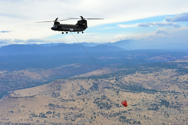 An Oregon Army National Guard CH-47 Chinook helicopter returns to the Madras Airport after successfully dumping water on a target area in the Logging Unit fire west of Madras, Ore., July 20, 2014. Two CH-47 Chinook helicopters and two HH-60M Black Hawk helicopters of the Oregon Army National Guard arrived at the Madras Airport the day before to assist local authorities in suppressing the wildfire west of Madras. U.S. Army photo by Staff Sgt. Jason Van Mourik