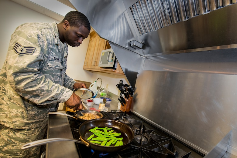 Staff Sgt. Phillip Burns II prepares Monterey chicken July 17, 2014, on Moody Air Force Base, Ga. Burns garnished his plate with sweet peas and mushroom sauce. He is a 23d Civil Engineer Squadron fire inspector. (U.S. Air Force photo/Airman 1st Class Ryan Callaghan)