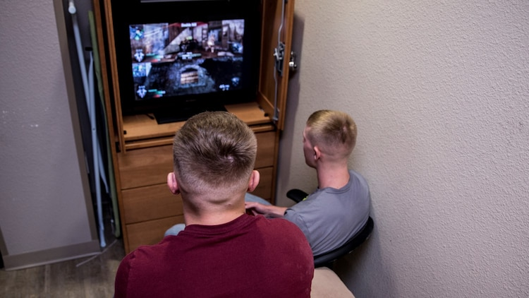Lance Cpl. Benjamin J. Provoznik, right, intelligence specialist, 15th Marine Expeditionary Unit, relaxes from the stressors of work by playing video games with a friend aboard Camp Pendleton, Calif., July 19, 2014. Provoznik, 19, is from Wilmington, Ohio. (U.S. Marine Corps video by Cpl. Emmanuel Ramos/Released)