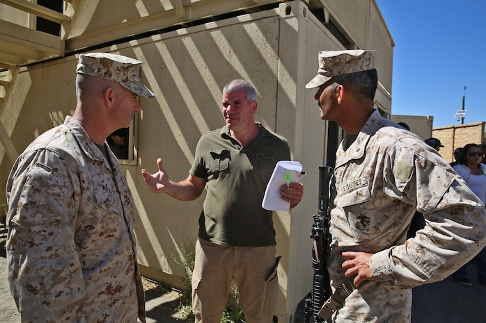 Erik Doman, center, a civil military cooperation representative with the United States Agency for International Development, talks to Col. Erik B. Kraft, left, Headquarters Regiment commanding officer, 1st Marine Logistics Group, and Lt. Col. Wilfred Rivera, right, Combat Logistics Battalion 15 commanding officer, HQ Reg., 1st MLG, during a humanitarian aid exercise as part of CLB-15's pre-deployment training taught by the Special Operations Training Group, 1st Marine Expeditionary Force, aboard Camp Pendleton, Calif., July 16, 2014. The exercise took place over the course of three days, and provided CLB-15  with a realistic and immersive experience. The simulation, set up by SOTG with the help of the USAID, put CLB-15's Marines and sailors in the middle of a typhoon-ravaged rural Philippine area where they were tasked with providing humanitarian aid and disaster relief, similar to the situation faced by  Marines with the 3rd Marine Expeditionary Force during the aftermath of Typhoon Haiyan in 2013. CLB-15 is slated to deploy with the 15th Marine Expeditionary Unit, 1st Marine Expeditionary Force.