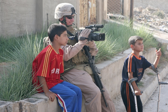 Staff Sergeant Christian Foucart, Second Marine Expeditionary Force (II MEF), Combat Camera video tapes a patrol in Al Fallujah, Iraq on September 5, 2007. Marines are assisting Iraqi Police in the distribution of food and soccer balls by proving transportation and security.   II MEF is deployed in support of Operation Iraqi Freedom in the Al Anbar province of Iraq to develop Iraqi Security Forces, facilitate the development of official rule of law through democratic reforms, and continue the development of a market based economy centered on Iraqi reconstruction. (Official USMC photo by MSgt Paul D. Bishop) (Released)