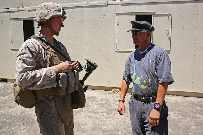 Private First Class Brandon Cleave, left, a motor vehicle operator with Combat Logistics Battalion 15, Headquarters Regiment, 1st Marine Logistics Group, builds rapport with Robert Alvarez Rey Casa, a role-player playing the role of a local government security official, during a humanitarian aid exercise as part of CLB-15's pre-deployment training with the Special Operations Training Group, 1st Marine Expeditionary Force, aboard Camp Pendleton, Calif., July 