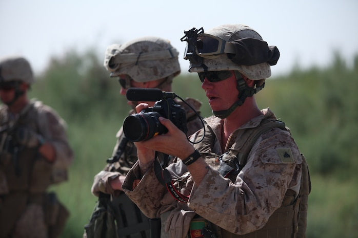 U.S. Marine Corps Cpl. Charles Mabry, a combat cameraman with the 2nd Marine Division Combat Camera, records video while working with Marines with the 2nd Light Armored Reconnaissance Battalion on patrol near Combat Outpost Castle, Helmand province, Afghanistan, May 30, 2011. The Marines patrolled the area to show continued presence and to provide security for the area. (U.S. Marine Corps photo by Chief Warrant Officer 2nd Class Clinton W. Runyon/Released)