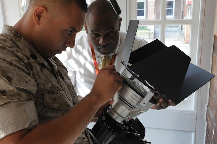 U.S. Marine Corps Sgt. Omar Elorza, left, a videographer assigned to Headquarters Marine Corps (HQMC) Combat Camera, and Rick Robinson, the head of the unit's video section, make adjustments on a studio light in preparation for an interview with retired Lt. Gen. John F. Sattler at Marine Barracks Washington's Center House in Washington, D.C., May 18, 2011. The interview was for a going-away video HQMC Combat Camera produced for Sgt. Maj. of the Marine Corps Carlton W. Kent. (U.S. Marine Corps photo by Lance Cpl. Cody A. Fodale/Released)