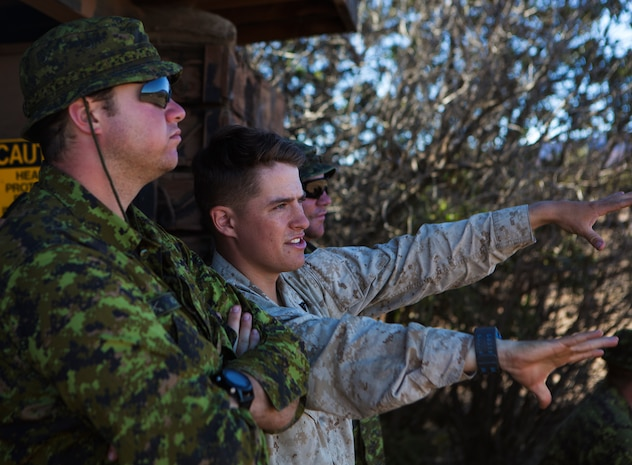 POHAKULOA TRAINING AREA, Hawaii - Cpl. Matthew Nolan, a Seattle native and the training noncommissioned officer with 3rd Battalion, 3rd Marine Regiment, speaks with a Princess Patricia's Canadian Light Infantry soldier about the range terrain prior to a live fire shoot, during the Rim of the Pacific (RIMPAC) Exercise 2014, July 18. Twenty-two nations, more than 40 ships and submarines, about 200 aircraft and 25,000 personnel are participating in RIMPAC from June 26 to Aug. 1 in and around the Hawaiian Islands and Southern California. The world's largest international maritime exercise, RIMPAC provides a unique training opportunity that helps participants foster and sustain the cooperative relationships that are critical to ensuring the safety of sea lanes and security on the world's oceans. RIMPAC 2014 is the 24th exercise in the series that began in 1971. (U.S. Marine Corps photo by Cpl. Erik Estrada/Released)