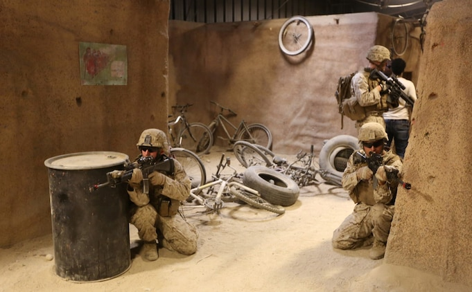 Marines with Company E, 2nd Battalion, 4th Marine Regiment, provide security during a training exercise aboard Marine Corps Base Camp Pendleton, Calif., July 16, 2014. The training was part of a battalion field exercise where Marines continued to improve their urban combat skills with the assistance of the Infantry Immersion Trainer. The IIT provides a training facility for practical application of tactical skills and decision making in an immersive, scenario-based training environment.
