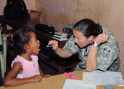 U. S. Army Capt. Emily Hollis examines a Honduran child during a MEDRETE.  Joint Task Force -Bravo's Medical Element (MEDEL), with support from 1-228th Aviation Regiment, JTF-Bravo Joint Security Forces and Army Forces Battalion, partnered with the Honduras Ministry of Health and the Honduran military to provide medical care to more than 650 people in the remote village of Barra Patuca in the Department of Gracias a Dios, Honduras, during a Medical Readiness Training Exercise (MEDRETE), July 17, 2014.  The multi-national team worked together to provide preventative medicine to the villagers, including classes on hygiene, preventative dental care, and nutrition. They also provided immunizations to infants, dental care, wellness checkups, medications, and minor medical procedures.  (Photo by U. S. Air National Guard Capt. Steven Stubbs)