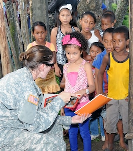 U. S. Army Capt. Erin Velazquez gives a Honduran child a Spanish reading book during a MEDRETE.  Joint Task Force -Bravo's Medical Element (MEDEL), with support from 1-228th Aviation Regiment, JTF-Bravo Joint Security Forces and Army Forces Battalion, partnered with the Honduras Ministry of Health and the Honduran military to provide medical care to more than 650 people in the remote village of Barra Patuca in the Department of Gracias a Dios, Honduras, during a Medical Readiness Training Exercise (MEDRETE), July 17, 2014.  The multi-national team worked together to provide preventative medicine to the villagers, including classes on hygiene, preventative dental care, and nutrition. They also provided immunizations to infants, dental care, wellness checkups, medications, and minor medical procedures.  (Photo by U. S. Air National Guard Capt. Steven Stubbs)