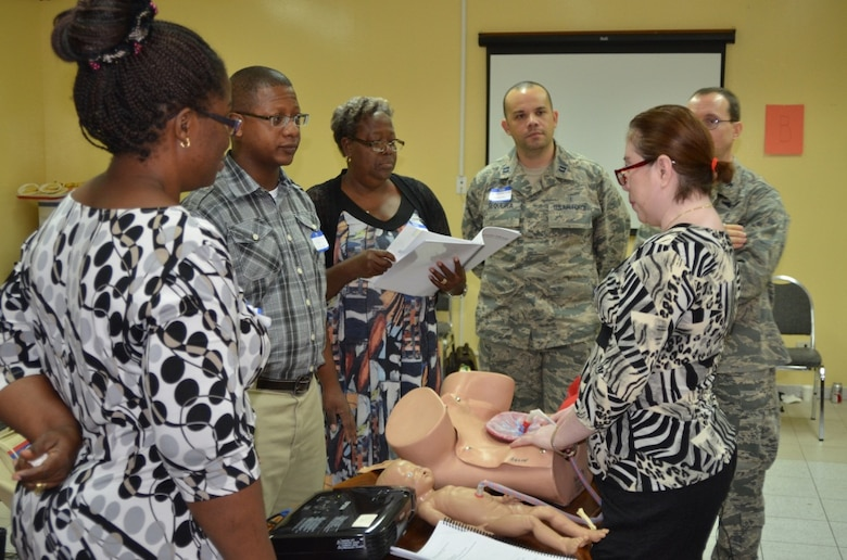 Belizean healthcare providers Uchenna Obasi, Dr. Desmond Arzu, Matron Matilda Mark and Rosanna Herstig practice group teaching at the Global ALSO Instructor Course, while Capt. Ricardo Sequeria and Col. Lyrad Riley, health care providers assigned to the 96th Medical Operations Squadron at Eglin AFB, monitor their progress  during the course in Belize City, Belize, June 22, 2014.  (Courtesy Photo)