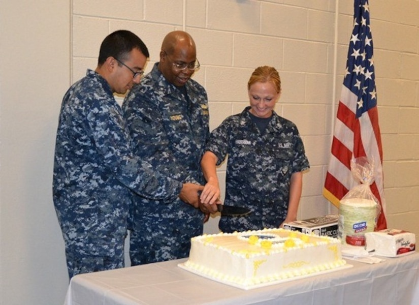 Rear Adm. Eric Young, deputy chief of Navy Reserve, center, participates in a cake cutting ceremony with Petty Officers 2nd Class James Rivas and  Megan Haberman as part of the Navy Operational Support Center Charleston celebration July 12, 2014 at Joint Base Charleston, S.C. (Courtesy photo)