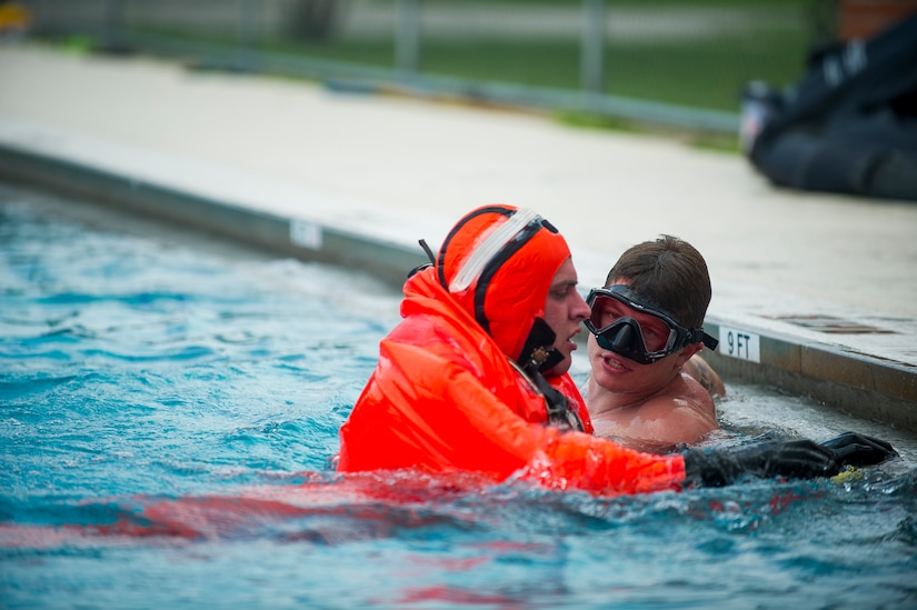 Petty Officer Toby Godwin, an instructor from the Naval Submarine School in Groton, Conn., offers words of encouragement as he assists a Naval Nuclear Power Training Command student practicing survival techniques inside a Submarine Escape Immersion Equipment suit July 17, 2014, at Joint Base Charleston, S.C Almost 150 enlisted NNPTC students received training on surface survival techniques and using SEIE. (U.S. Air Force photo/Senior Airman George Goslin)