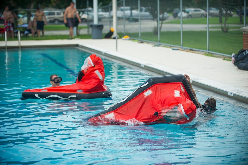 Petty Officer Toby Godwin and Chief Petty Officer Jason Counts, both instructors from the Naval Submarine School in Groton, Conn., assist Naval Nuclear Power Training Command students as they practice survival techniques inside a Submarine Escape Immersion Equipment suit July 17, 2014, at Joint Base Charleston, S.C Almost 150 enlisted NNPTC students received training on surface survival techniques and using SEIE. (U.S. Air Force photo/Senior Airman George Goslin)