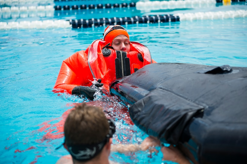 Petty Officer 3rd Class Toby Godwin, an instructor from the Naval Submarine School in Groton, Conn., assists a Naval Nuclear Power Training Command student as he practices survival techniques inside a Submarine Escape Immersion Equipment suit July 17, 2014, at Joint Base Charleston, S.C Almost 150 enlisted NNPTC students received training on surface survival techniques and using SEIE. (U.S. Air Force photo/Senior Airman George Goslin)