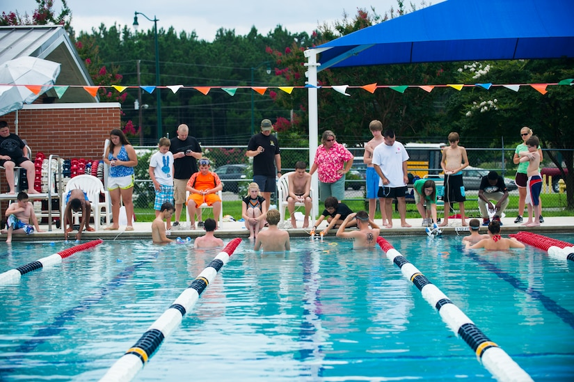 Dependent children immerse their SeaPerch submarines into a pool for a team based competition, July 18, 2014, at Joint Base Charleston, S.C. The teams competed by using their submarines to pick up rings in the pool. (U.S. Air Force photo/Senior Airman George Goslin)