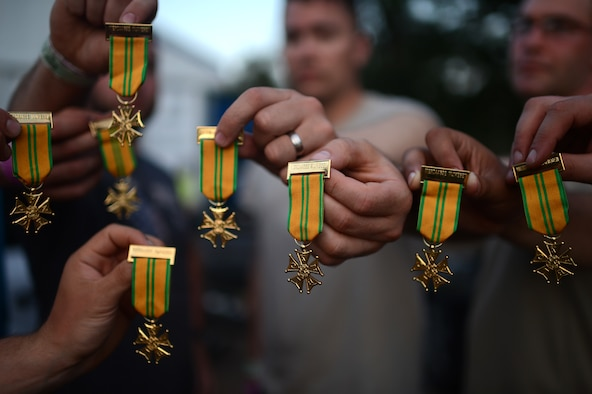 Finishers of the International Four Days Marches Nijmegen from the U.S. Army 361st Civil Affairs Brigade and U.S. Air Force 52nd Fighter Wing hold up their completion medals in Nijmegen, the Netherlands, July 18, 2014. Throughout the week, 39,910 civilians and military members from countries around the world completed the march to receive their medal. (U.S. Air Force photo by Senior Airman Gustavo Castillo/Released)