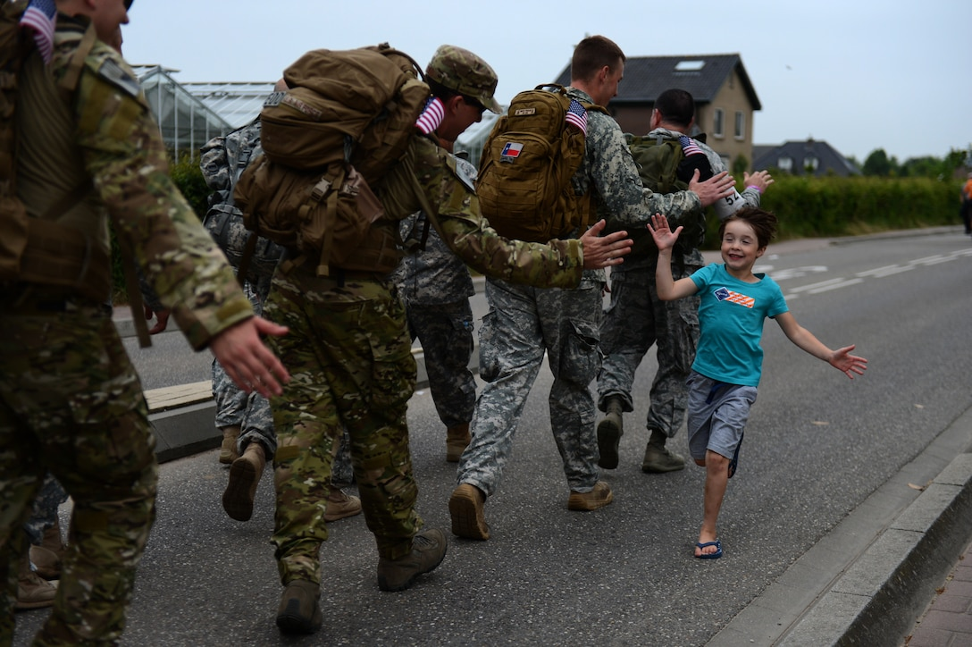 A child celebrates with International Four Days Marches Nijmegen participants from the U.S. Army 361st Civil Affairs Brigade and U.S. Air Force 52nd Fighter Wing before crossing a bridge in Nijmegen, Netherlands, July 15, 2014. Military participants gave out small souvenirs to on looking children cheering and celebrating throughout the march. (U.S. Air Force photo by Senior Airman Gustavo Castillo/Released)