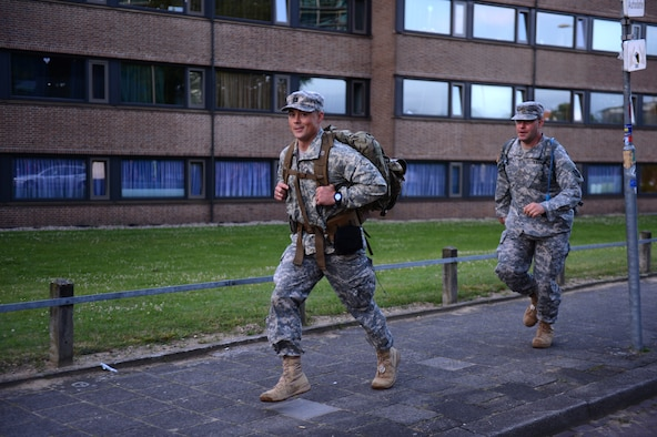 U.S. Army Capt. David Esra and 2nd Lt. Christopher Bulger, members of the 361st Civil Affairs Brigade ruck team run to catch up to their formation during the International Four Days Marches Nijmegen in Nijmegen, Netherlands, July 15, 2014. Each day there was a time limit given to the marching participants in which they had to complete a certain amount of miles to continue throughout the week. (U.S. Air Force photo by Senior Airman Gustavo Castillo/Released)