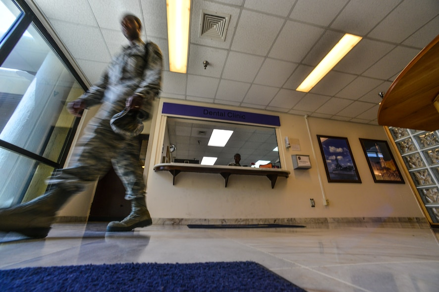 An Airman exits the 39th Medical Group after visiting the dental clinic July 22, 2014, Incirlik Air Base, Turkey. The 39th MDG dental clinic supports active duty service members at Incirlik AB, Izmir Air Station and 717th Air Base Squadron in Ankara, Turkey.  (U.S. Air Force photo by Senior Airman Nicole Sikorski/Released)