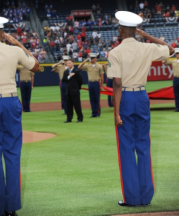 Marines, lining the bases, salute during the singing of the national anthem and presentation of colors during the Atlanta Braves' Marine Corps Appreciation Day game, July 19 at Turner Field in Atlanta, Georgia.