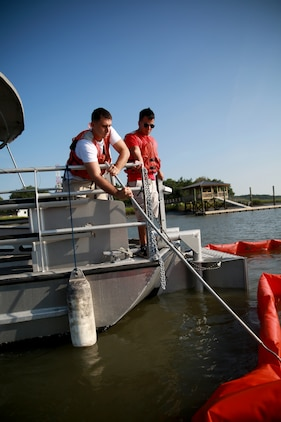 Corporal Joseph Bartelt (left), a native of Jacksonville, Fla., and Lance Cpl. Otto Villavicencio (right), a native of Miami, both Aircraft Rescue and Firefighting specialists with Headquarters and Headquarters Squadron aboard Marine Corps Air Station Beaufort, position a boom designed to trap oil contamination in water during a week-long training course designed to increase proficiency in nautical spill response procedures aboard MCAS Beaufort, July 17. The course enabled the students to evaluate environmental and nautical conditions and tactics in order to hastily respond to an oil spill in the waterways leading to MCAS Beaufort.