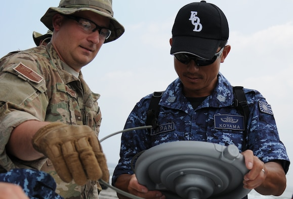 Staff Sgt. Justin Walter, right, explains to Japanese Maritime Self-Defense Forces Senior Petty Officer Akira Koyama where the fuse wiring on the explosive device goes July 15, 2014, at the Draughon Bombing Range, Misawa Air Base, Japan. The Japanese EOD members got to work hands-on with equipment used by U.S. military EOD forces. Walter is a 35th Civil Engineer Squadron EOD craftsman and Koyama is a Japanese EOD member. (U.S. Air Force photo/Senior Airman Jose L. Hernandez-Domitilo)