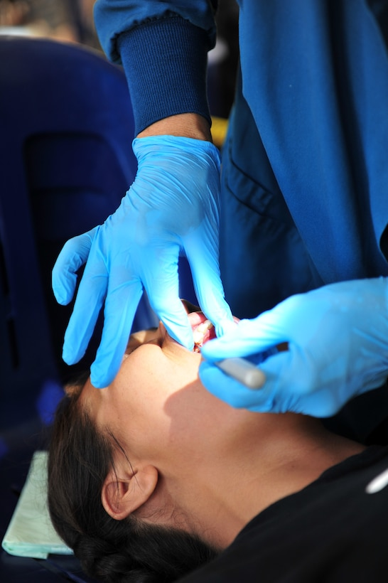 Lt. Col. Catherine Kanwetz  performs an extraction July 22, 2014, in Neiafu, Tonga. Pacific Angel-Tonga includes general health, dental, optometry, pediatrics, and engineering programs as well as various subject-matter expert exchanges. Kanwetz is deployed from the 152nd Air Base, Reno, Nev., and is the PACANGEL-Tonga lead dentist. (U.S. Air Force photo/Staff Sgt. Rachelle Coleman)