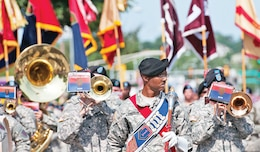 Sgt. 1st Class Troy Swanson, the 1st Inf. Div. Band's senior noncommissioned officer, leads the band July 4 as they play and march in the annual Sundown Salute parade in Junction City. The band later performed at the Wamego fireworks show.