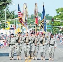 A color guard from the 4th IBCT, 1st Inf. Div., carries the American, Army, 1st Inf. Div. and Kansas colors at the front of the Sundown Salute parade July 4 in Junction City.