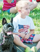 Six-year-old Henry Kreinbrink and his best friend, AbbyLou, both Fort Riley residents, watch the Sundown Salute parade July 4 in Junction City. Junction City hosted its annual Independence Day celebration July 2 to 5, drawing thousands to the community for four days of family activities that included a carnival, concerts, fun runs, parade and fireworks. Hundreds of 1st Infantry Division and Fort Riley Soldiers marched in the July 4 parade, representing every unit on post.