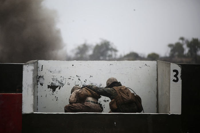 POHAKULOA TRAINING AREA, Hawaii - Marines with Headquarters Battery, 1st  Battalion, 12th Marine Regiment, duck behind a barrier after throwing a grenade at Range 5C in Pohakuloa Training Area, Hawaii, July 20, during Rim of the Pacific (RIMPAC) Exercise 2014. The Marines are a part of Company Landing Team 2, which include Indonesian marines, Australian and Tongan soldiers. Twenty-two nations, more than 40 ships and submarines, about 200 aircraft and 25,000 personnel are participating in RIMPAC from June 26 to Aug. 1 in and around the Hawaiian Islands and Southern California. The world's largest international maritime exercise, RIMPAC provides a unique training opportunity that helps participants foster and sustain the cooperative relationships that are critical to ensuring the safety of sea lanes and security on the world's oceans. RIMPAC 2014 is the 24th exercise in the series that began in 1971. (Photo by Sgt. Sarah Dietz/Released)