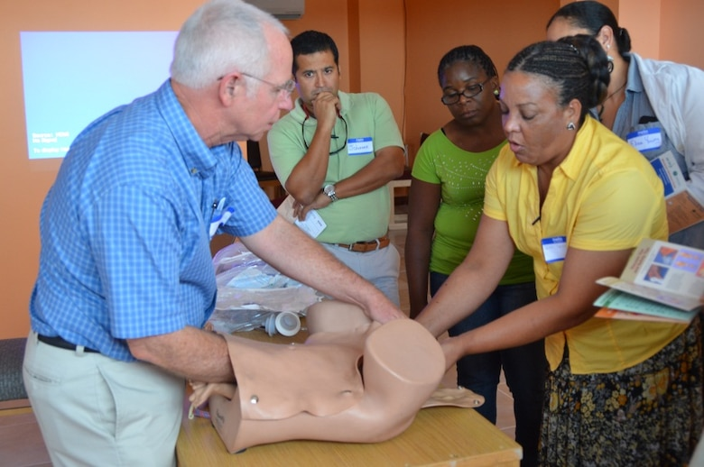 Dr. Robert Persons, Doctor of Osteopathic Medicine and Fellow of the American Academy of Family Practice and Joan Arana teach a group of Belizean healthcare professionals how to perform an assisted vaginal delivery during the Global Advanced Life Support in Obstetrics Instructor Course in Belize City, Belize, July 23, 2014. (Courtesy Photo)