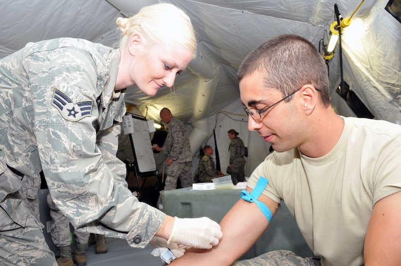 Senior Airman Kristen Hill (left) and Airman 1st Class Paul Longwroth (right) from the Nevada Air National Guard 152nd Medical Group hone their skills of performing medical lab work in field conditions during the National Guard PATRIOT 2014 exercise at Volk Field, Wis. Several units of the Air National Guard, Army National Guard and Reserve units from several states are working with local, state, and national organizations to train on, perform, and assess their ability to respond to multiple emergencies.