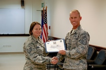 U.S. Air Force Chief Master Sgt. John Weimer, 386th Air Expeditionary Wing former command chief [Southwest Asia], presents Tech. Sgt. Leda Brienza, 727th Special Operations Aircraft Maintenance Squadron knowledge operations technician currently assigned to the 386th Expeditionary Operations Group as an administrative assistant, with her Rock University certificate June 19, 2014 at an undisclosed location in Southwest Asia. Brienza is among the first to graduate from the program since its inception last April. (U.S. Air Force courtesy photo)