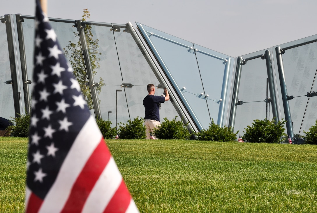 Master Sgt. Jeffrey Scobee, Team Buckley Top 3 member, cleans the Colorado Freedom Memorial July 18, 2014, in Aurora, Colo. Buckley Air Force Base members have begun the new initiative to take care of the memorial at least once every month. (U.S. Air Force photo by Staff Sgt. Nicholas Rau/Released)