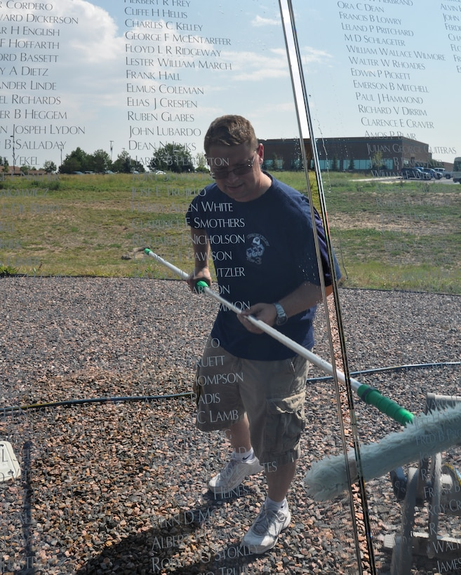 Master Sgt. Robert Holeman, Team Buckley Top 3 member, cleans the Colorado Freedom Memorial July 18, 2014, in Aurora, Colo. Buckley Air Force Base members have begun the new initiative to take care of the memorial at least once every month. (U.S. Air Force photo by Staff Sgt. Nicholas Rau/Released)