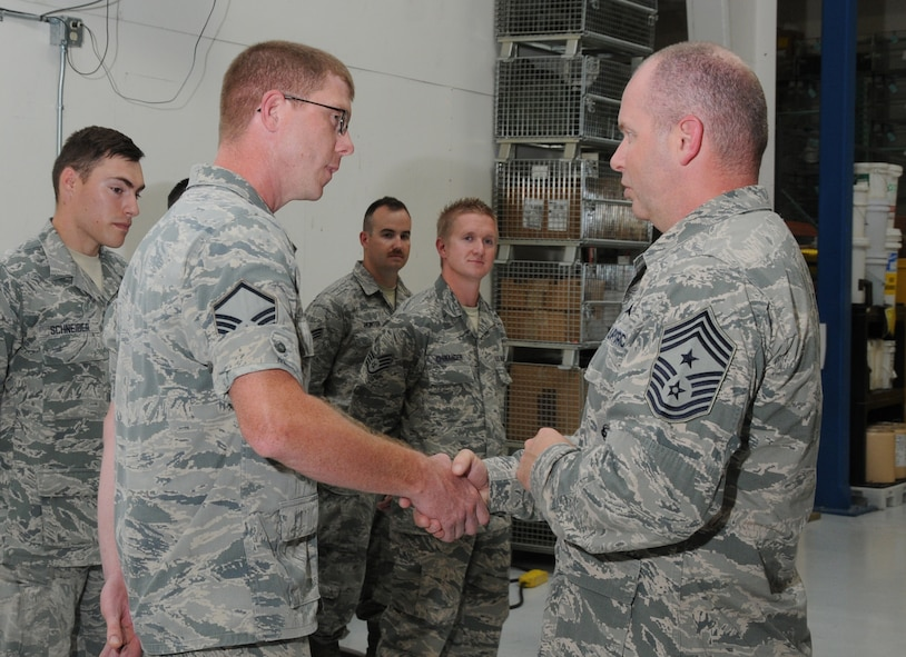 U.S. Air Force Master Sgt. Michael Moore, 270th Air Traffic Control Squadron, is coined by Chief Master Sgt. James W. Hotaling, the Air National Guard Command Chief, during Hotaling's visit to Kingsley Field, Klamath Falls, Ore. July 15, 2014. Hotaling spent the day meeting and speaking with the Airmen of the 173rd FW and 270th Air Traffic Control Squadron. (U.S. Air National Guard photo by Master Sgt. Jennifer Shirar/Released)