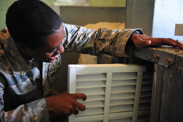 Airman 1st Class Malik Gomes, 8th Civil Engineer Squadron Heating, Ventilation, Air Conditioning and Refrigeration shop journeyman, replaces multiple air filters in an air handler at Kunsan Air Base, Republic of Korea, July 23, 2014. Changing air filters is one of the preventative maintenance measures performed on HVAC equipment to keep it running and ensure mission essential facilities and equipment are kept cool. (U.S. Air Force photo by 1st Lt. Earon Brown/Released)