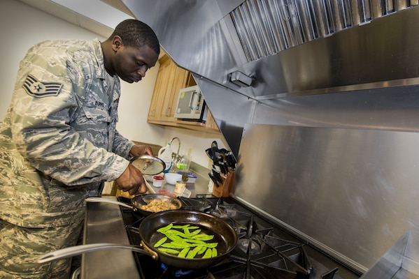 Air Force Staff Sgt. Phillip Burns II prepares Monterey chicken July 17, 2014, on Moody Air Force Base, Ga. Burns garnished his plate with sweet peas and mushroom sauce. He is a 23rd Civil Engineer Squadron fire inspector. U.S. Air Force photo by Airman 1st Class Ryan Callaghan